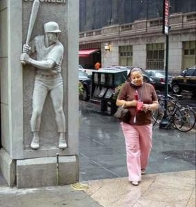 a statue about to hit a woman with a baseball bat