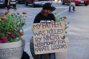 homeless guy with a sign about ninjas killing his dad
