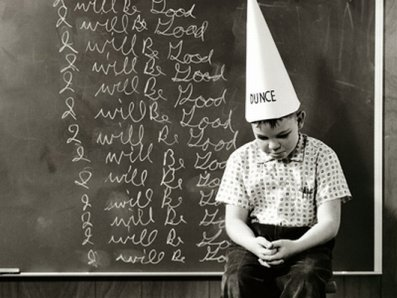 kid in dunce cap writing I will be good on the chalk board